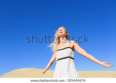 Happy woman enjoying sun and freedom under hot sun and blue sky in desert. Smiling young blonde female model free outside. - stock photo