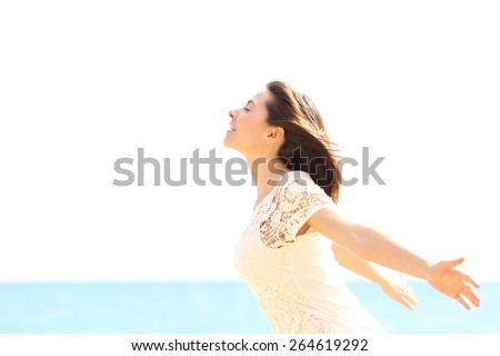 Happy woman enjoying the wind and breathing fresh air on the beach in a sunny and windy day - stock photo