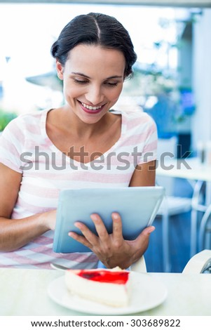 Happy woman enjoys using her tablet in a cafe