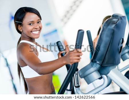 Happy woman exercising at the gym on an x-trainer - stock photo