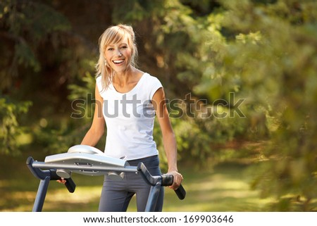 Happy woman exercising on the treadmill outdoors