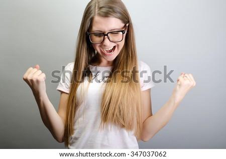 happy woman exults pumping fists celebrates success - stock photo