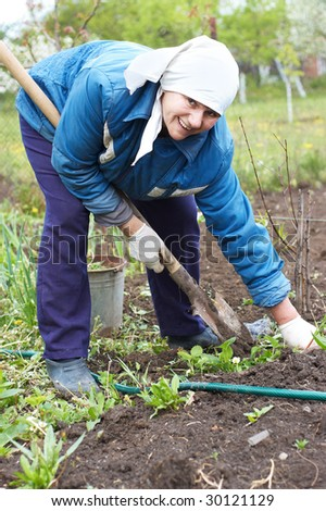 Happy woman farmer digging with spade