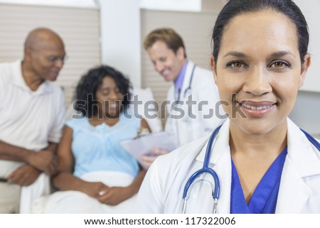 Happy woman female Hispanic Latina Doctor in hospital with patient recovering in hospital bed & male doctor in background