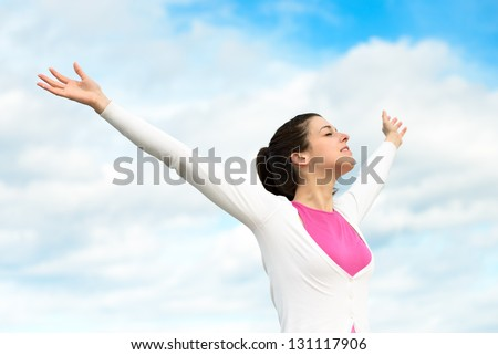 Happy woman freedom blissful concept. Woman with arms up raised to sky relaxing on spring / summer holidays outdoors. Caucasian brunette girl model. - stock photo