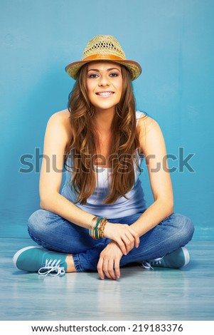 happy woman full body portrait . girl sitting on a floor in teenager style .  crossed leg - stock photo