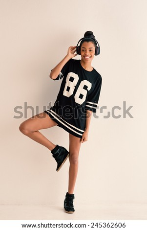 Happy woman full body portrait with headphones. Filtered image. - stock photo