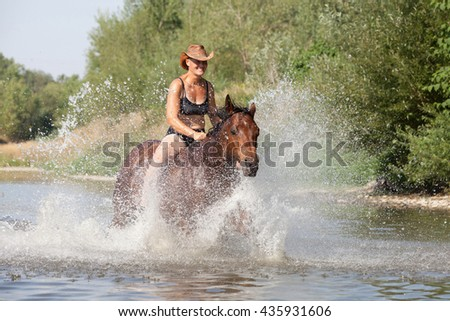 Happy woman galloping in the water