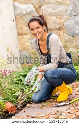 Happy woman gardening fall yard housework flowerbed hobby - stock photo