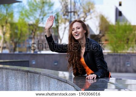Happy  woman greeting friend on street - stock photo