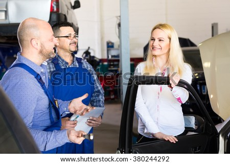 Happy woman has brought her car to dealership for maintenance service
