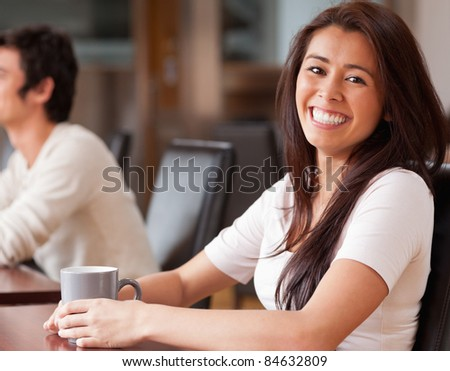 Happy woman having a coffee in a cafe - stock photo