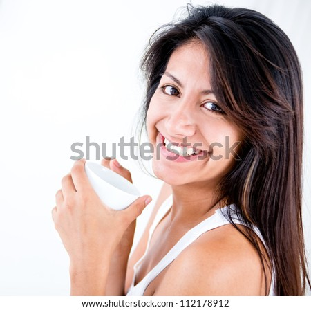 Happy woman having a hot drink and smiling - stock photo