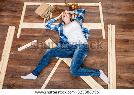 Happy woman having fun assembling furniture at home. Young girl laying on floor arranging apartment house interior. DIY. High angle view. - stock photo