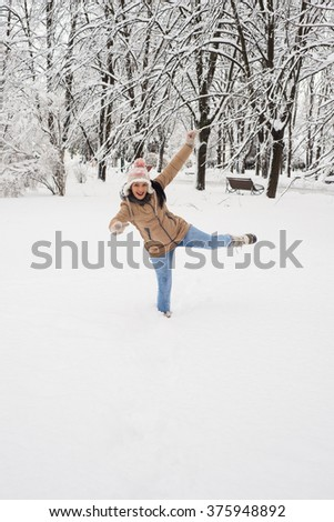 Happy woman having fun in the snow  in park - stock photo