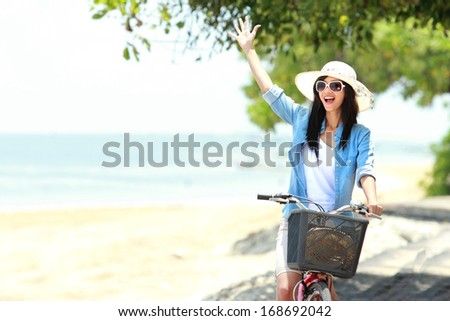 happy woman having fun riding bicycle and raised her arm - stock photo