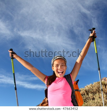 Happy woman hiker holding her arms in the air in a feeling of success having reached the summit. From a hike / backpacking trip in the beautiful  volcanic landscape on the volcano, Teide, Tenerife. - stock photo