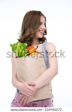 Happy woman holding a shopping bag full of groceries and looking away - stock photo