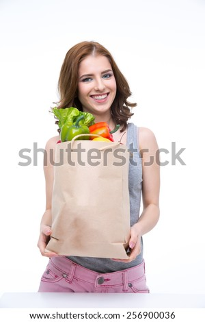 Happy woman holding a shopping bag full of groceries and looking on at camera - stock photo