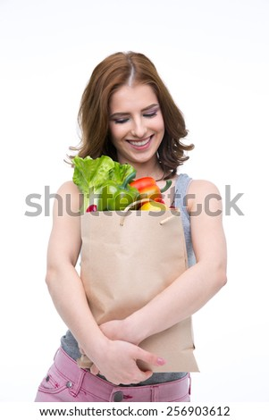 Happy woman holding a shopping bag full of groceries and looking on it - stock photo