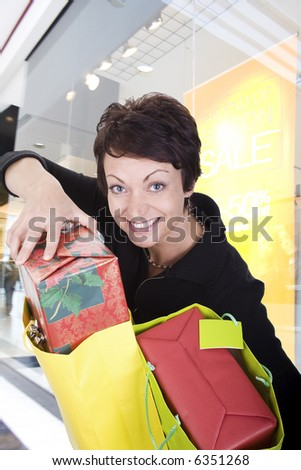 happy woman holding bags shopping in mall