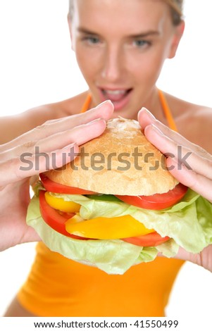 Happy woman holding big burger - stock photo