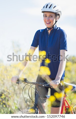 Happy woman holding bike looking at camera - stock photo