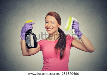 Happy woman holding brush and detergent cleaning solution bottle  - stock photo