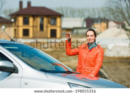 happy woman holding car and house keys