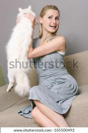 happy woman holding cat while sitting in couch