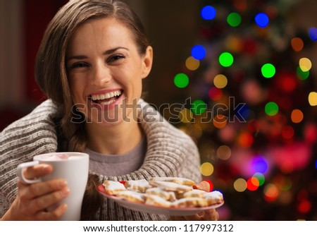 Happy woman holding cup of hot chocolate with marshmallows and plate of Christmas cookies - stock photo