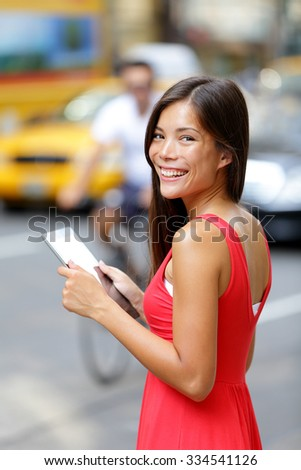 Happy woman holding digital tablet while standing on city street. Side view of young female is wearing red dress. Smiling beautiful woman is with tablet PC on street in city. - stock photo