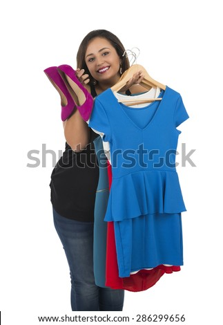 Happy woman holding dresses and heels against a white background - stock photo