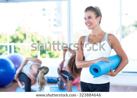 Happy woman holding exercising mat in fitness studio - stock photo