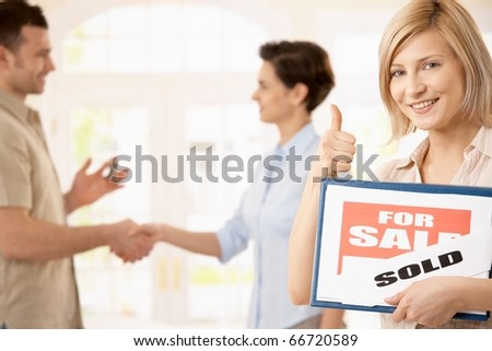Happy woman holding for sale sign giving the thumb up, smiling man shaking hands with estate agent in background.? - stock photo