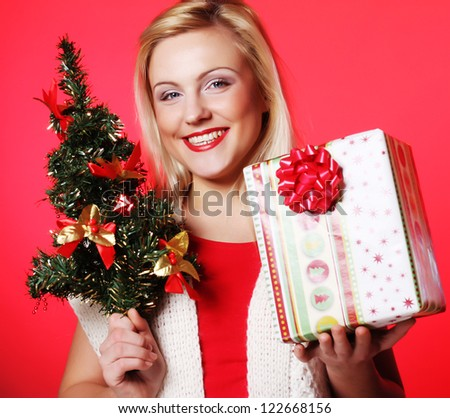 happy woman holding gift  and the tree