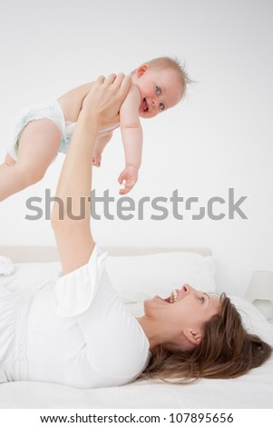 Happy woman holding her baby while lying in a bedroom - stock photo
