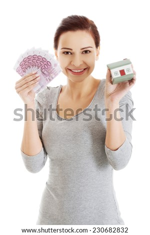Happy woman holding house model and euro bills.