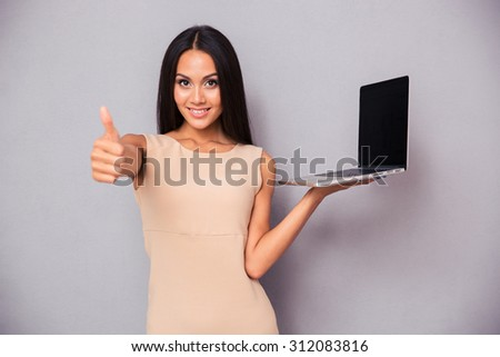 Happy woman holding laptop and showing thumb up over gray background. Looking at camera - stock photo