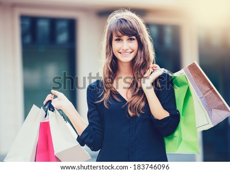 Happy woman holding shopping bags and smiling at the mall - stock photo