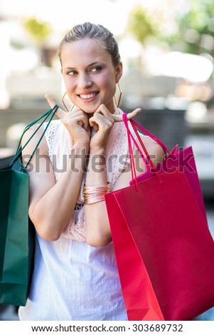 Happy woman holding shopping bags at the mall
