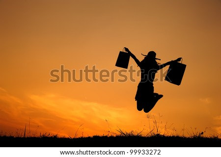 Happy Woman holding shopping bags jumping in sunset silhouette - stock photo