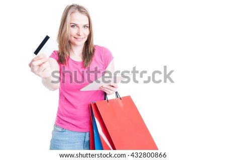 Happy woman holding tablet with shopping bags offering debit card to buy something isolated on white with advertising area - stock photo