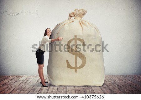 Happy woman hugging a big bag of money, grey wall on background