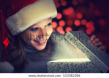 happy woman in a Christmas cap opens the magic box gift - stock photo