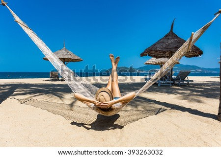 Happy woman in a hammock enjoying vacation on tropical beach - stock photo