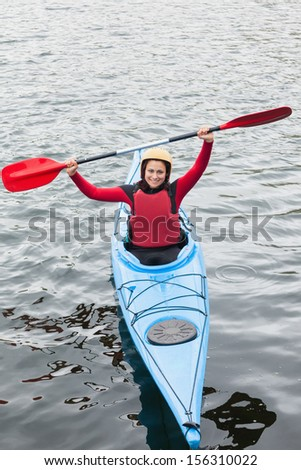 Happy woman in a kayak cheering at the camera in the middle of a lake - stock photo