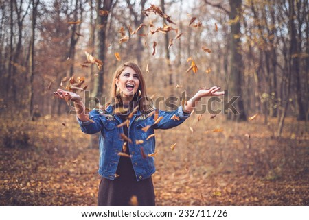 Happy woman in a romantic autumn fall scenery throwing leaves wearing a fashion denim jacket with geometric print - stock photo