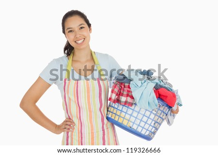 Happy woman in apron holding full laundry basket - stock photo