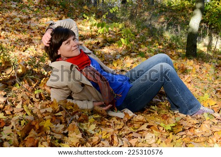 Happy woman in autumn park - stock photo